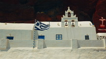 Greek Flag Flying Next to a Traditional White Cycladic Church with a Volcanic Red Cliff in the Background