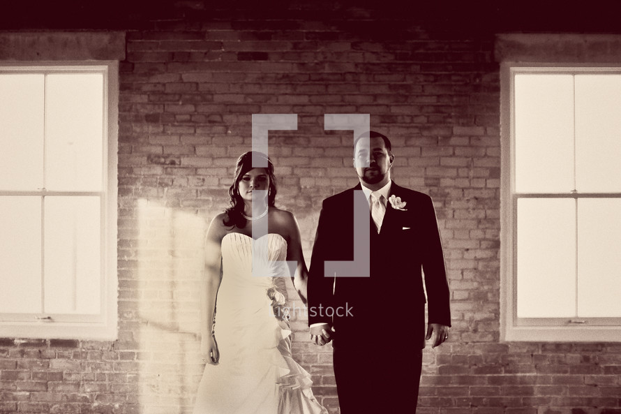 bride and groom standing in front of a brick wall
