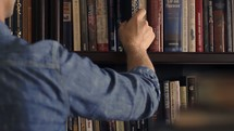 a man picking a book from a bookshelf