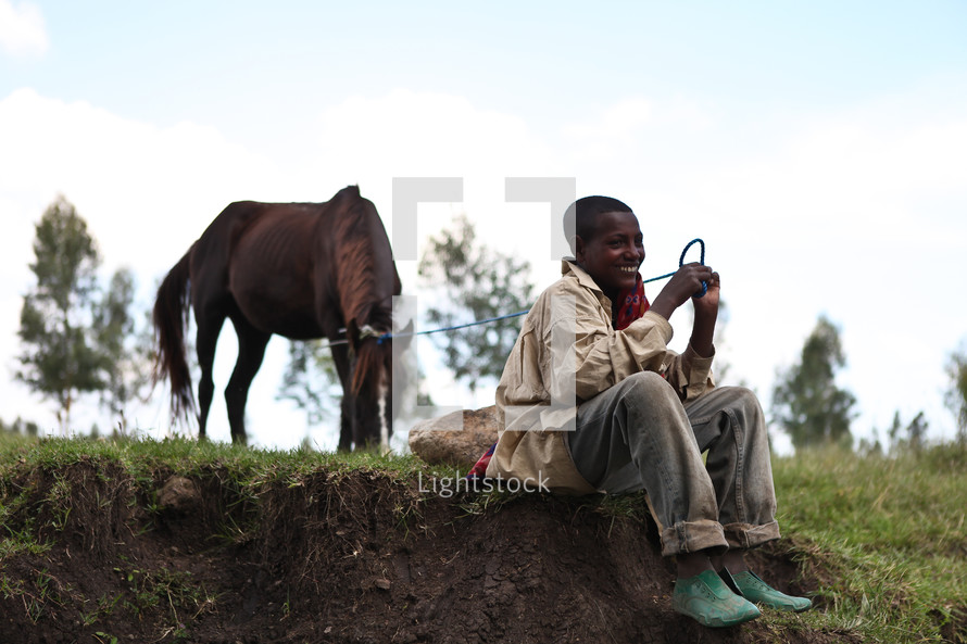 Ethiopian boy sitting and letting a horse graze