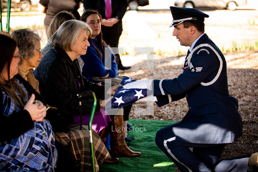 Widow of veteran accepts the burial casket flag from the honor guard during the graveside service of her husband. She receives it with a resolute smile of strength, hope and peace she has as a result of her deep faith in Jesus Christ.