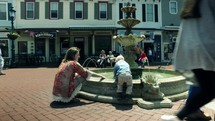 mother and toddler boy playing in a fountain