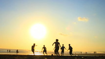 teen boys playing soccer on the beach at sunset