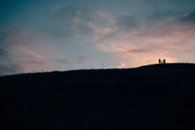 silhouette of a family on a hilltop