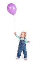 toddler girl holding a purple balloon