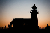 silhouette of a lighthouse at sunset