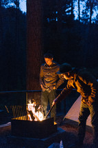 men standing near a campfire at night