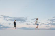 walking barefoot on sand dunes at dusk