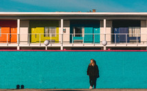 a young woman standing in front of a rainbow colored motel