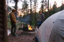 men standing by a camp fire