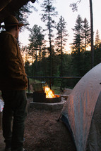 man standing near a tent and campfire