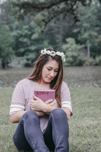 a woman with flowers in her hair holding a Bible