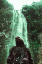 a person standing in front of a waterfall