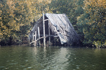 straw hut over a river