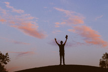 silhouette of a man with raised hands holding a Bible