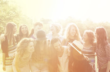 group of friends laughing standing under intense sunlight
