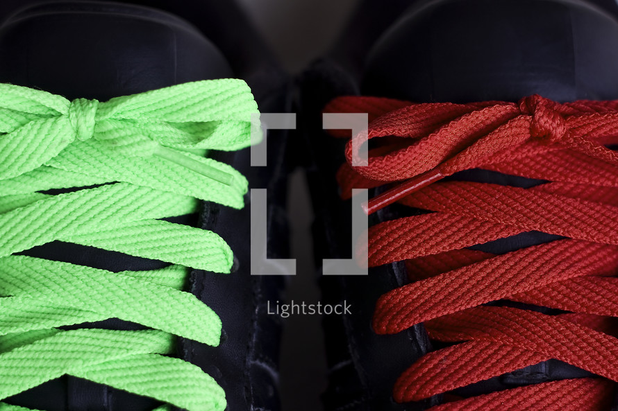 green and red shoe laces on a pair of black shoes