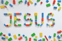 colorful wooden toy blocks lettering the name JESUS