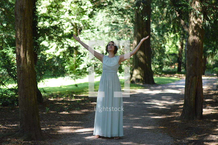 a woman in a long dress standing on a path in a forest with raised hands