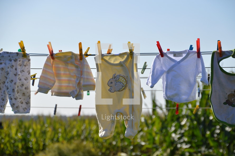 baby clothes drying at a laundry line.  family, baby, clothes, washing, toddler, happy, dry, wet, drying, outdoor, hanging, hang, new, Christmas, born, newborn, little, small, child, children, kid, kids, playsuit, babygrow, rompers, romper suit, babywear, wear, wearing, baby clothes, baby garments, garments, clothesline, line, clothes line, laundry, laundry line, washing line, dry off, air, offspring, junior, generation, grow, growing, growth, descendants, descendant, increase, increasing, fruitful, birth