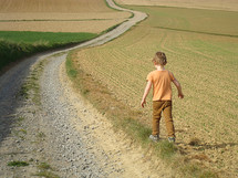 Child walking along a winding road through the countryside.