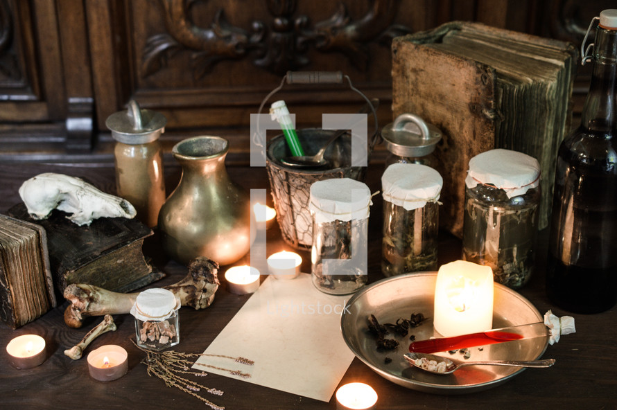 vintage Apothecary - or: eerie witches' kitchen with lot of ingredients for a potion, a blank sheet of paper for the recipe or greetings and ancient gruesome jars dark with only candlelight for Halloween