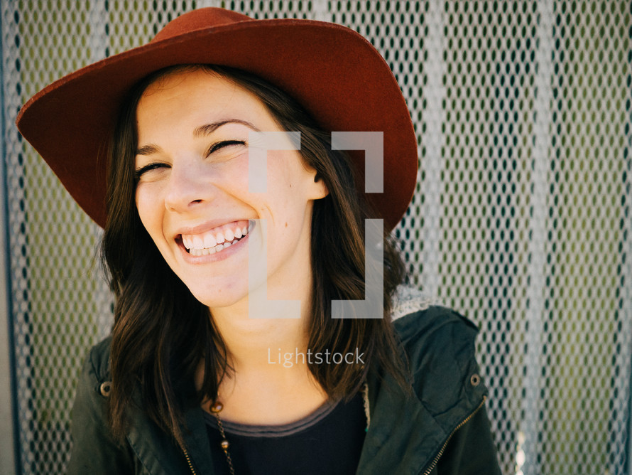 A laughing young woman in a red hat.