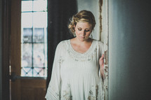 Pensive woman standing in the hallway of a house.