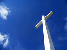 The glory of The Cross. A white cross stretches out to Heaven against a bright and blue sky towering above the clouds and the world to reveal the hope and glory of Jesus Christ.