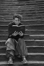 woman sitting alone on stone steps reading a Bible