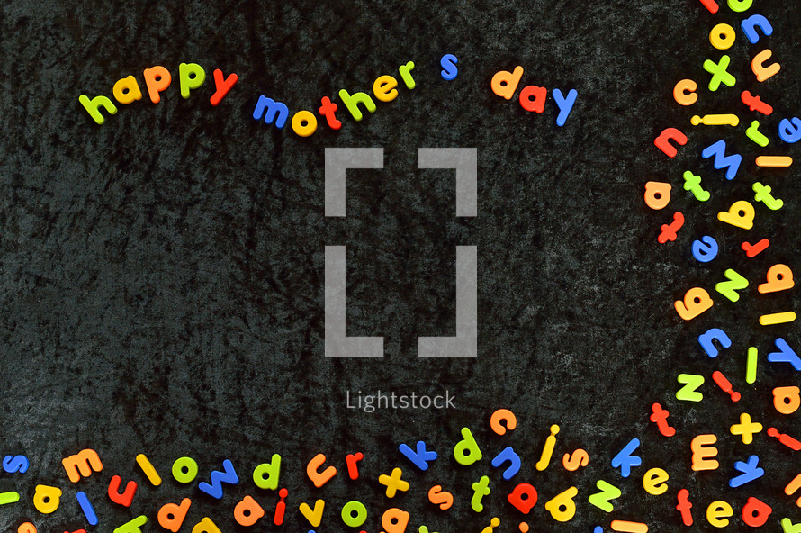 many magnetic letters and the words HAPPY MOTHER'S DAY on black velvet ground.