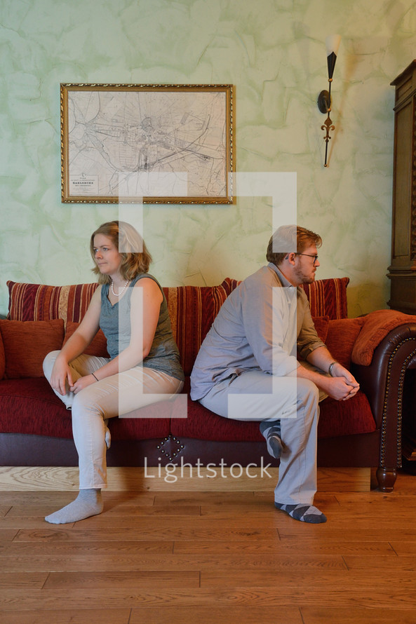 arguing couple sitting turned away from each other on a couch