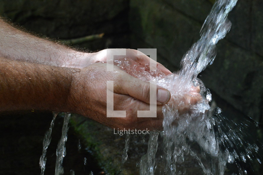 a man washing his hands under water
