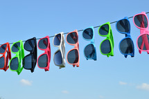 sunglasses hanging on a wire against a blue sky