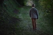 little boy walking alone through a dark ravine forest in late evening