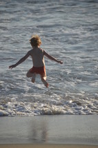 Little boy jumping in the waves with flying hair and having fun