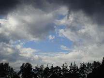 blue sky piercing through dark clouds,