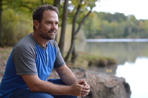 a man outdoors at a lake shore with clapped hands