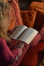 woman reading her bible comfortably on a sofa at home