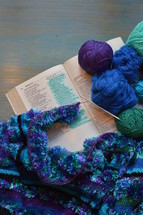 wool and a piece of knitting on a bible open at the page of Proverbs 31: The Wife of Noble Character with the line: She selects wool and flax marked