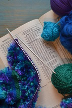 wool and a piece of knitting on a bible open at the page of Proverbs 31: The Wife of Noble Character with the line: She selects wool and flax underlined