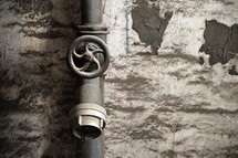 Pipe faucet and handle on a brick wall.