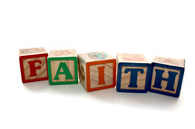 Children's building blocks spelling out Faith on white background.