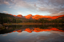reflection of red rock mountains and sky in lake water