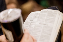 a person with a coffee cup and Bible in their lap