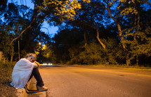 Woman sitting on the side of the road at night.