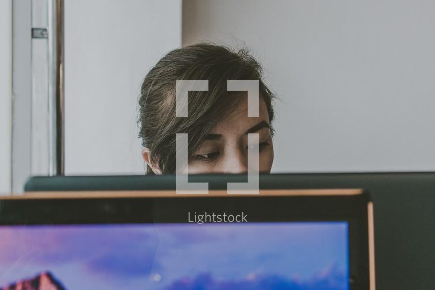 a woman behind a computer screen photo by jonathan querubin