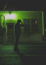 man standing in a dark alley with his hand on his head