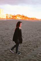 a woman walking on a beach in sneakers