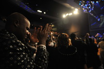 Man with hands raised praising God during worship service.